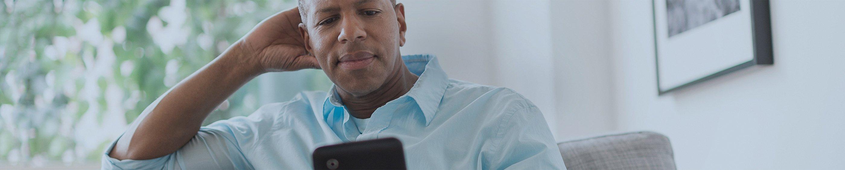 Un padre leyendo su tablet en el sofá