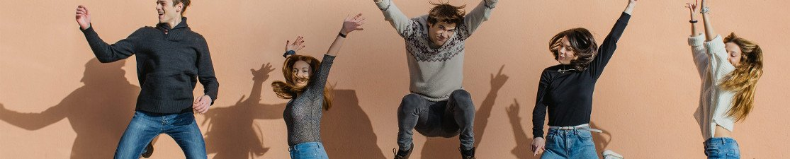 Un grupo de amigos saltando con sus manos en el aire riendo y sonriendo