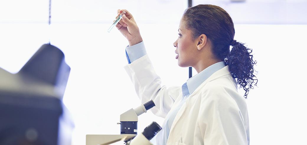 Un doctor en una bata de laboratorio inspeccionando un tubo de ensayo