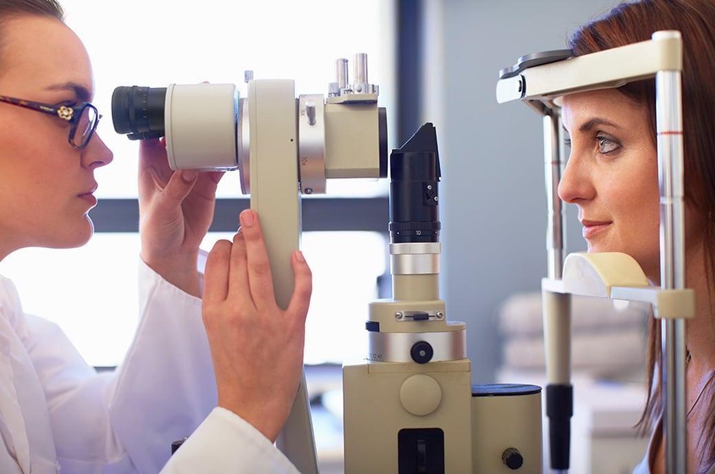 Una vista lateral de un profesional de la visión y una mujer joven mirando a través de una cámara de retina