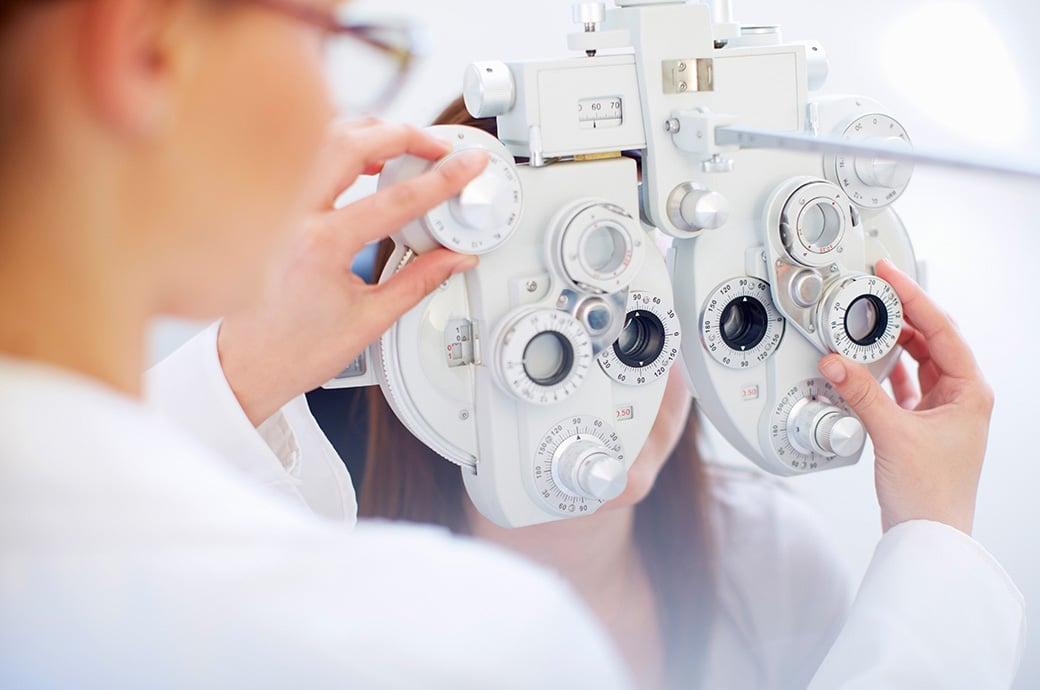 Una mujer joven detrás de un foróptero mientras el profesional de la visión revisa sus ojos durante un examen ocular