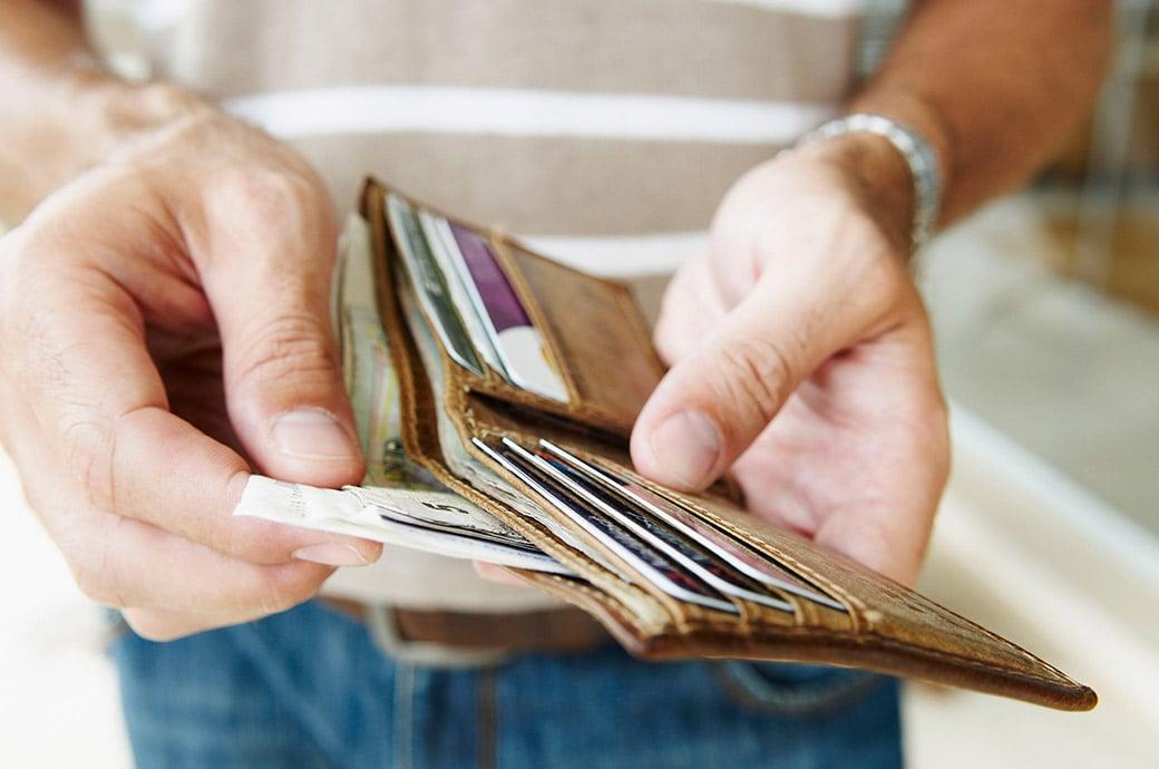 Un acercamiento de alguien sacando billetes de una cartera