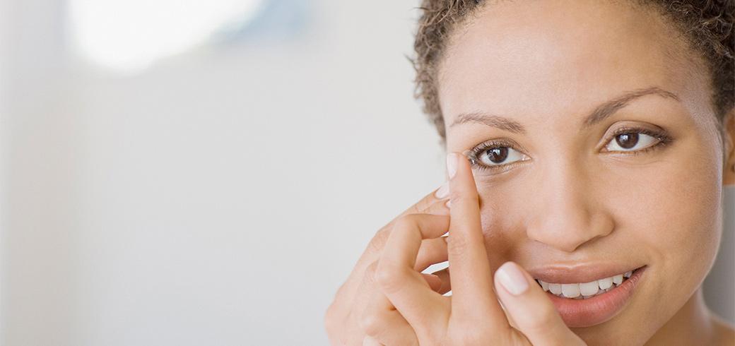 Una mujer con un lente de contacto en su dedo a punto de ponerlo en su ojo]